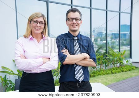 Corporate Portrait Of Two Smiling Office Employees Outdoors. Middle Aged Business Man And Woman Posi