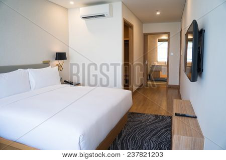 Small Hotel Room Interior With Double Bed And Bathroom. Double Bed With White Sheets Complemented Wi