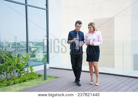 Two Confident Business Colleagues Walking On Office Terrace. Mid Adult Business Man And Woman Discus