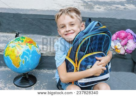 First-grader Boy Is Sitting With A Backpack On The Doorstep Of The School. Bouquet And Globe. The Fi