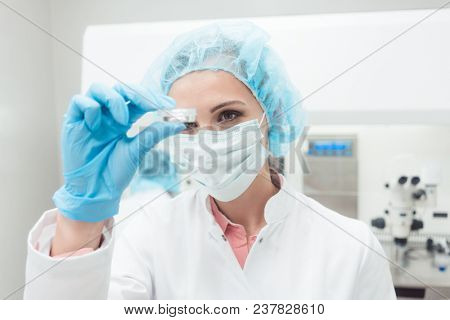 Woman scientist showing her newest biotech experiment in lab petri dish