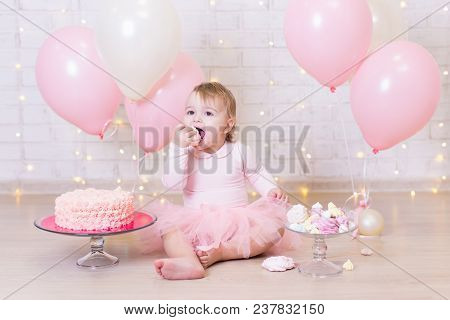 Birthday Party Concept - Funny Little Girl Eating Cake Over Brick Wall Background With Lights And Co