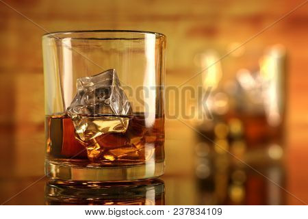Chilled Whiskey Glass With Ice Cubes With Bokeh In The Background
