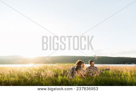 Group of friends in landscape at sundown playing guitar music poster