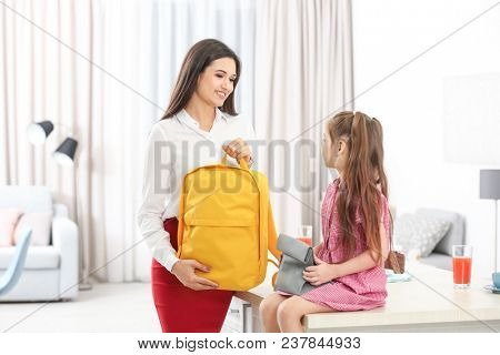 Young mother helping her daughter get ready for school