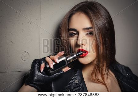 Modern Girl Smoking Vape. Trendy New Vaping Device, Smoke E-liquid Instead Of Nicotine Cigarettes. T