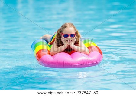 Child On Inflatable Float In Swimming Pool.