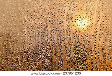Raindrops On The Windowpane With Sunset Background