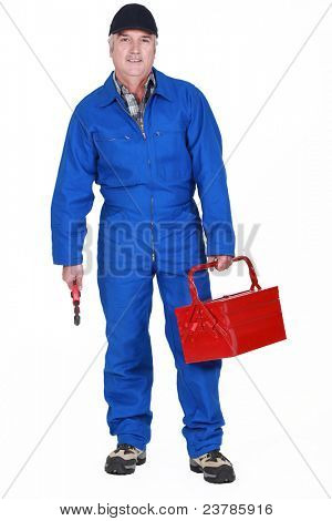 Tradesman holding a tool and his toolbox