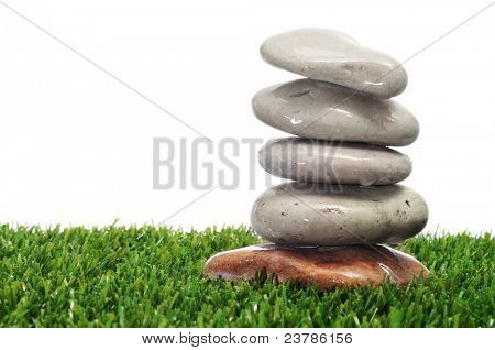 a pile of stones on the grass on a white background