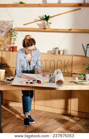 Stylish Young Female Artist In Eyeglasses Artist Painting At Table In Studio