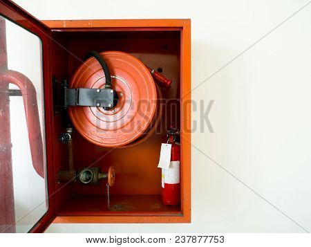 Fire Extinguisher With Various Types Of Fire Extinguishers Located In The White Wall. Copy Space For