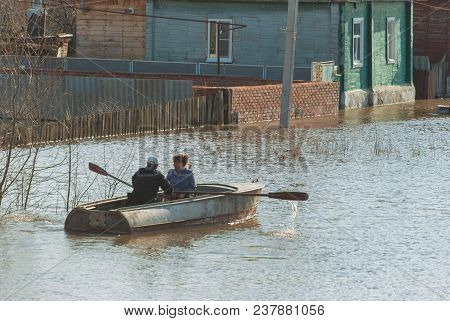Russia, Balashov April 24, 2018. People In A Boat Sail Along A Flooded Street To Their House. Sunken