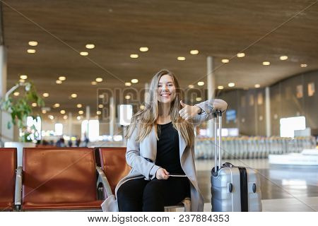 Nice Girl Making Video Call By Modern Tablet In Airport Waiting Room And Sitting Near Grey Valise, S
