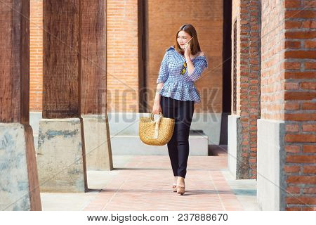 Happy Young Asian Woman In Nice Casual And Comfortable Clothes Walking Casually At Her Local Shoppin