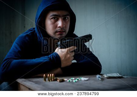 Traders Sell Drugs - Buy Drugs. His Hand Holds A Gun On The Table. Have Moneys, Drugs And Syringe On