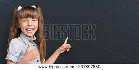 Back To School Concept. Portrait Of Happy Young Student On Dark Background. Child Smiling And Lookin