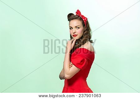 Beautiful Young Woman With Pin-up Make-up And Hairstyle At Studio. Pensive And Pretty Female Caucasi