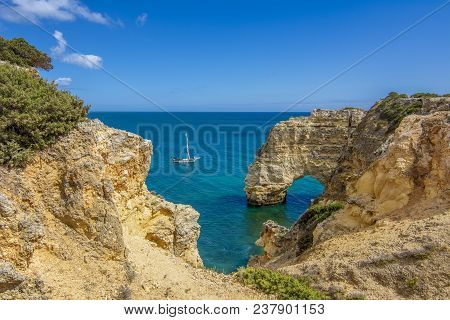 Rock Cliff Arche On Marinha Beach And Turquoise Sea Water On Coast Of Portugal In Algarve Region