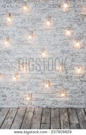 Light Bulbs On White Brick Background With Wooden Floor. Vintage Edison Light Bulbs Garland In Loft