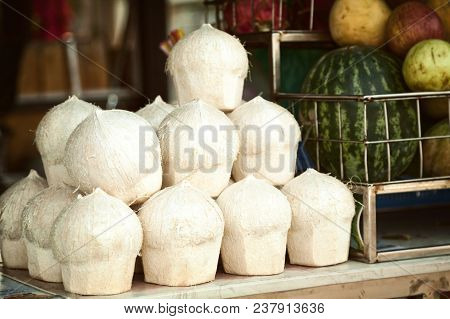 Pile Of Peeled Cocos For Drinking On A Market Stall. Many Coconuts And Other Fruit For Sale At A Sup
