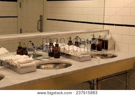 Long Sink And Countertop Filled With Rolled Facecloths And Various  Hand Creams And Soaps For Guests