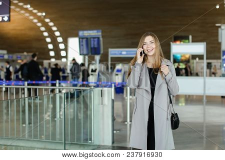 European Businesswoman Talking By Smartphone At Airport Hall, Wearing Grey Coat And Bag. Concept Of