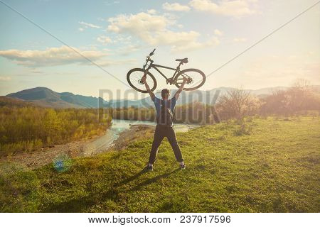Boy Cyclist Standing On A Mountain And Looks At The River At Sunset A Cyclist Holds A Bicycle Over H