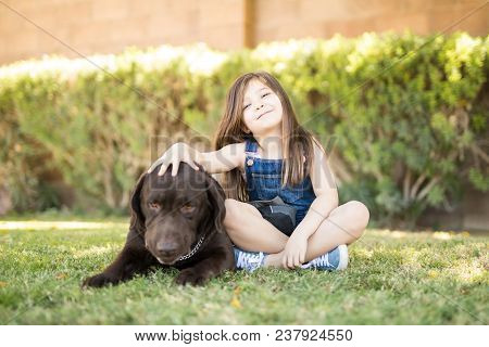 Portrait Of A Cute Little Adorable Child Sitting In Park With Chocolate Labrador Best Friend.
