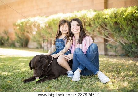 Pretty Young Mother With Daughter Sitting On Pet Dog In House Back Garden During A Summer Day.