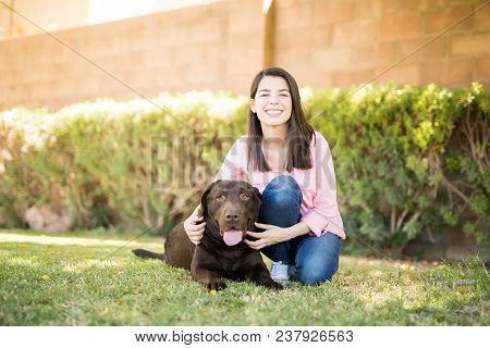 Portrait Of A Beautiful Young Woman In Jeans Sitting On Grass With Pet Doggy.