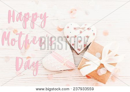 Happy Mother's Day Text On Cookie Hearts And Gift Box On White Rustic Wooden Background With Confett