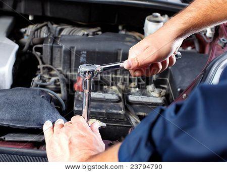 Mãos de mecânico trabalhando na oficina de reparação automóvel.