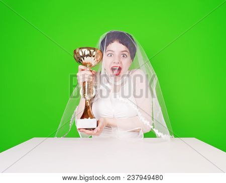 Caucasian Bride In A Wedding Attire Holding A Golden Trophy. Half Length Of Young Brunette With A Tr