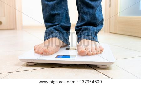 Closeup Image Of Barefoot Person Standing On Digital Scales