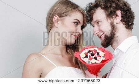 Loving Couple With Candy Bunch Bouquet Flowers. Handsome Man And Pretty Woman Holding Present Gift.