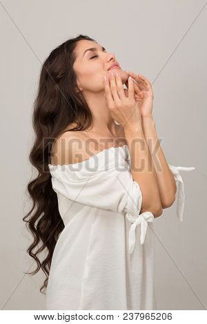 Young Brunette Woman With Long Brown Curly Hair Standing Half Turn. Beauty Concept. Mid Age Woman Ov