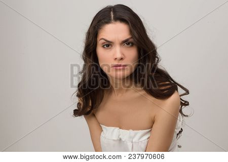 Close Up Of Beautiful Brunette Adult In White Dress With Angry Face. Isolated On White Background. M