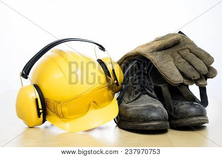 Protective Helmet And Work Boots On A Wooden Table. Safety And Health Protection Accessories For Con