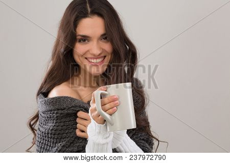Smiling Brunette Model In Gray Cardigan Holding Cup Of Coffee. Isolated On White Background. Mid Age