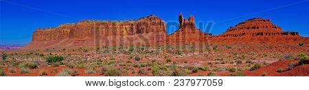A panorama view of Monument Valley's three famous formations known as Eagle Mesa, the Sitting Hen, and Douglas Butte. This is composed of 5 sequential photos stitched together. Monument Valley straddles the border of Arizona and Utah on the Navajo In poster