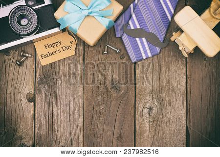 Happy Fathers Day Gift Tag With Top Border Of Gifts, Ties And Decor On A Rustic Wood Background. Top