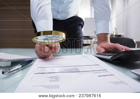 Human Hand Holding Magnifying Glass Over Invoice