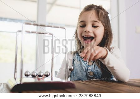 Child Playing And Learning With Newton's Cradle