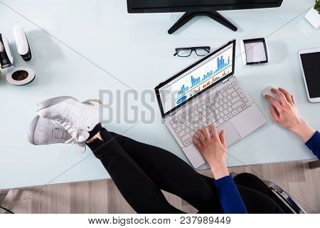 Businessperson's Hand Analyzing Graph On Laptop