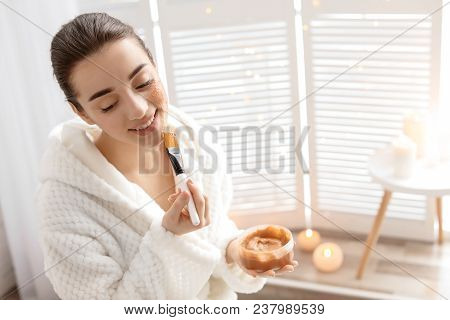 Young Woman Applying Natural Scrub On Face In Bathroom