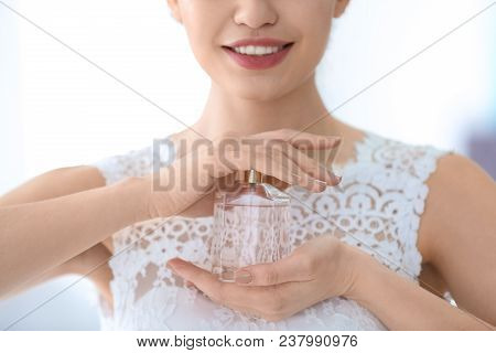 Beautiful Young Bride With Bottle Of Perfume On Light Background, Closeup