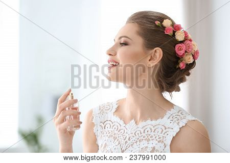 Beautiful Young Bride With Bottle Of Perfume On Blurred Background