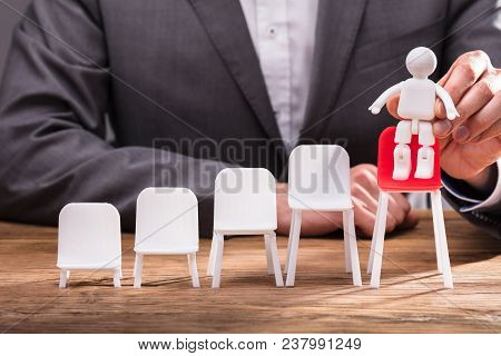 Businessperson Placing Human Figure On Red Chair