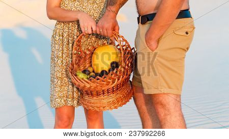 Couple Holding A Wicker Basket With Fruit, Man And Woman Having A Picnic On The White Sand Beach Or